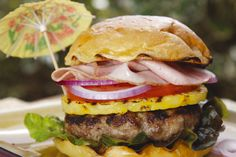 Hawaiian Luau Burger is made up of a pork patty topped with tomatoes, onions and grilled pineapple along with shaved smoked ham