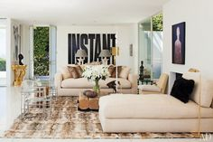 Neutral living room with furry rug, chaise lounges, modern side chairs, and eclectic art