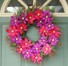 . This is a twig style wreath, about 18-19 inches from twig tip to twig tip. It is covered with beautiful purple and dark pink flowers. The flowers