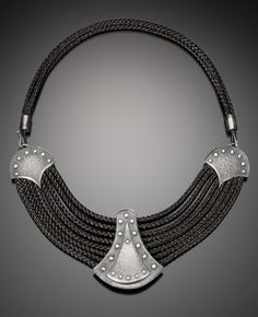 """Donna Veverka,  """"A deep passion for history & architecture inspire my jewelry. Thick rings, wide bracelets, & forged chains connect the wearer to an ancient, romantic world. Symmetry of repeated arches, clusters of spires, & lines of intricate tracery were decorative elements used for centuries to impress. Leather, hammered metal, & rivets are powerful elements that render elegantly wearable, sophisticated design. Blade forms & battlements once protected castles now guard fingers and…"""