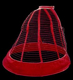 Cage crinoline of steel with red wool and linen, 1860-1865. Via the Victoria and Albert Museum
