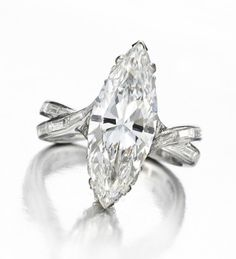A Diamond Ring, centering upon a marquise-cut diamond, weighing approximately 4.72 carats, flanked by fluted upturned basket set with marquise-cut diamonds, woven marquise-cut diamond band, mounted in platinum, total weight, circa 1950.  Available at FD Gallery, New York