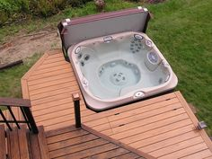 """Timbertech """"Tropical Teak"""" composite decking with hidden fasteners around a hot tub with access hatch for tub."""