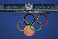 The full moon rises through the Olympic Rings hanging beneath Tower Bridge during the London 2012 Olympic Games August 3, 2012. | REUTERS/Luke MacGregor