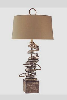 Hand-forged iron rings sit in a tumbled stack atop a cubic base in this distinctive table lamp from John Richard. A hand-painted scorched silver and gold multi-step finish gives this piece a wonderful patina. Bronze drum shade and matching finial complete the design. #tablelamp #modernlighting #lighting #lightingfixtures. *aff*