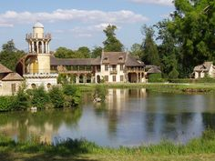 The Hameau de la Reine (The Queen's Hamlet) -rustic retreat in the park of the Château de Versailles built for Marie Antoinette in 1783 near the Petit Trianon in the Yvelines, France. It served as a private meeting place for the Queen and her closest friends, a place of leisure.  It contained a meadowland with lakes and streams, a classical Temple of Love on an island with fragrant shrubs and flowers, an octagonal belvedere, with a neighboring grotto and cascade.