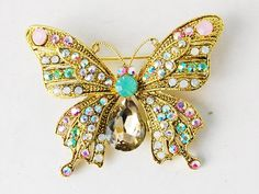 $9.99 Designed in a gold-tone alloy metal, this shimmery butterfly brooch is enhanced with crystal rhinestones and light pastel colored rhinestones. One center pacific opal rhinestone completes the heavenly feel that this butterfly provides. It is approximately 2 inches by 1.5 inch, great for decoration and wear! Blouses, purses, scarves, you name it. This butterfly is perfect for everything