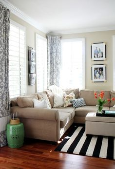 My couch is beige, and I love how they used the black and white rug with the couch.