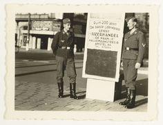 Anonymous | Luftwaffe militairen op straat, Anonymous, 1941 | Twee Luftwaffe militairen staan op straat bij een reclamebord voor ijzerhandel De Haan&Co in de Halvemaansteeg in Amsterdam. Zij staan dus op het Rembrandtplein.