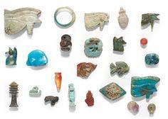 Lot d'environ VINGT AMULETTES représentant en autre des yeux-Oudjat, Thouéris, un dieu-enfant, un coeur, un djed. Faïence siliceuse et pierres diverses. Égypte et Proche-Orient, IIe-Ier millénaires av. J.-C. Dim_de 0,8 cm à 4 cm