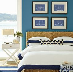 Crisp blue and white nautical bedroom with Ship Blueprints above headboard.