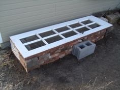 Use old bricks and door for cold frame.  The transparent top admits sunlight and prevents heat escape via convection that would otherwise occur, particularly at night. Essentially, a cold frame functions as a miniature greenhouse to extend the growing season.