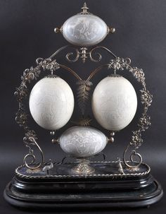 VICTORIAN AUSTRALIAN TABLE CENTREPIECE formed as FOUR mounted EMU AND OSTRICH EGGS carved with kangaroo, an aborigine and emu, set in a plated frame with leaves and flowers.
