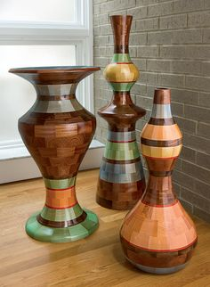 Stunning wood vessels by Joel Hunnicutt created from dozens of small, precisely cut blocks built into a rough form and then turned on a lathe to transform them into intriguing, totem-like sculptures.