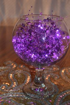 "A simple, inexpensive Centerpiece:  RENTAL PRICE:  $5.50.  This centerpiece consists of the SULLIVAN GIFTS' 5' ""Lavender/Purple Beaded Ornament Garland;"" (RENTAL PRICE:  $1.50); Purple LED String Light Garland (RENTAL PRICE:  $3.00); and any simple $1.00 bowl.  PLEASE NOTE:  sample display…beaded garland and LED lights rented separately."