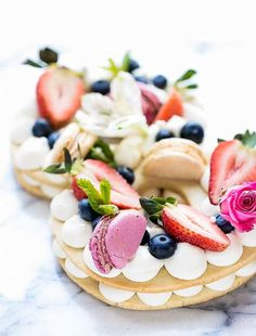 Cream Tart Recipe - New Cake Trend - festive double decker cake, with cream between the layers and on top, topped with berries, meringues and macarons.