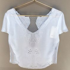 "Gorgeous Cropped V-Neck Lace Inset Blouse Beautifully detailed crop top features 100% Rayon fabric with embroidered cut work lace detailing featuring delicate lace insets at lower sides and back. Approximately 21-23"" shoulder to hem. Stunningly gorgeous! Available  in Juniors Sizes: S/3-5 M/7-9 L11-13. Color: Ivory. No trades ever Tops Crop Tops"