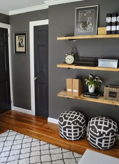 light colored wood floating shelves in front of a grey graphite wall