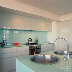 Kitchen with modern glass splash back In a galley kitchen, white handleless units and a granite counter create a smart, streamlined look, while a glass splashback reflects plenty of light. Description from pinterest.com. I searched for this on bing.com/images