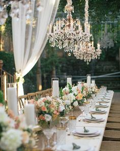 Wooden tables and chairs decorated with taupe sequin runners, oversized French candlesticks, and crystal chandeliers | @cjevans325 | Brides.com