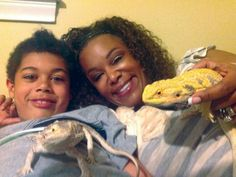 A mother and son bonding with their pet iguanas
