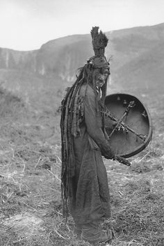 Mongolian shaman wearing a ritual gown and holding a drum with the image of a spirit helper, c. 1909. National Museum of Finland