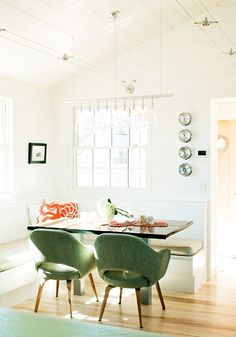 A light-filled breakfast nook with silk-screened pillows and vintage chairs.