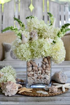Create a flower arrangement and centerpiece for your table incorporating seashells. This easy tutorial adds some seaside charm and interest to your glass vase, in addition to a decorative way to conceal your flower stems. ©homeiswheretheboatis.net #flowers #DIY #seashells #arrangement Diy Summer Flower Arrangements, Beautiful Flower Arrangements, Summer Flowers, Diy Flowers, Floral Arrangements, Beautiful Flowers, Flower Centerpieces, White Flowers, Table Arrangements