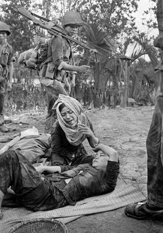 As South vietnamese troops pass by in the Ca Mau peninsula, a mother grieves over her daughter, who was badly wounded by machine gun fire from a U.S. helicopter, the week of Sept. 15, 1963. The soldiers had landed by helicopter in response to an attack by Viet Cong guerrillas on a South Vietnamese outpost. (AP Photo/Horst Faas) ~ Vietnam War