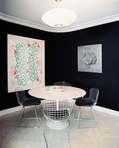 A tulip table and metal Bertoia chairs surrounded by black walls. Interior Design: Laura Garcia