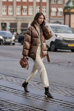 Le Fashion: An Elevated Street Style Take on the Puffer Coat — Winter outfit idea with a brown puffer coat, a beige turtleneck sweater, mini camel bag, off-white pants, and square-toe ankle boots