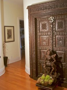 Designer Marie Burgos uses an intricately carved wall decor, a carved statue of the Hindu god, Vishnu, and a portrait of Gandhi to create a calm and peaceful entryway. Neutral walls illuminate the details of the elaborate wooden focal point.