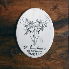 """***PLEASE NOTE*** THIS ITEM SHIPS 2-3 DAYS AFTER PAYMENT ………………………………………………………………………………….  """"O dry bones, Hear the Word of the Lord. Ez 37:4 oval wood sign with cow skull wearing flower garland  The Goods: -Material: Oval Wood plaque -Measurements: 11 x 14 -Background: white -Lettering: black -Image: black -Back of Sign: unfinished with a sawtooth hanger -Sign is distressed  ***All of my signs are one of a kind. No two will ever be the same.*** …………………………………………………………………………………..  Follow me on…"""