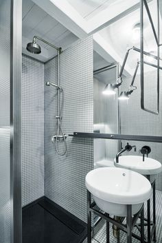 The industrial aesthetic might be strongest in the second of the two bathrooms, where a wireglass shower divider and metal washbasin support were custom fabricated by the Czech workshop kurel. The tap is from Bonigio, the washbasin itself is from Sanindusa, and the lamp is another Tolomeo Micro Parete from Artemide.