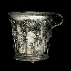 """The treasure of Boscoreale, buried just before eruption of Vesuvius in 79, yielded a pair of gilded silver cups which have skeletons under a garland of roses. Greek inscription: """"Enjoy while you're alive, the future is uncertain. """""""