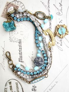 """4 Strands Complicated Bracelet with Aqua and Be Prepared This 4 strand bracelet has 2 vintage, rhinestone bracelets. Both are prong set. One is clear rectangular stones and the other is round aqua stones. Strand number 3 is a made up of 4 different chains and interrupted by a repurposed aqua and white enamel tie clip, a vintage Boy Scouts """"Be Prepared"""" pin from which I hung a wonder repurposed writing award pin. Strand number 4 is made up of 2 different vintage rosaries, one in ..."""