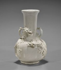 """Chinese white glazed porcelain vase; of bottle form with two contesting dragons moulded in high relief, possibly 18th century; H: 12"""""""
