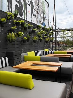 Casual Rooftop Terrace -Bright yellow pops against sedate black, white and grey cushions.  A graphic, abstract mural by Balint Zsako and a wall of hanging garden pots contrast the clean-lined loungers of the Drake Hotel's Sky Yard bar.