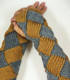 Made using a technique called entrelac, these gloves are knitted on the diagonal in a basket weave pattern. They have a ribbed cuff around the arm for a more comfortable fit, and a crochet edge around the hands for snugness.