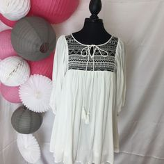 Tapestry embroidered bodice dress. Rust or White, both are beautiful! The white looks awesome with black leggings & a pair of the ever popular ankle bootie. Tassel tie and 3/4 sleeve. Front is slightl