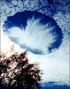 Per Dan Ashbach, this is a rare meteorological phenomenon called a skypunch. Ice crystals form above the high-altitude cirro-cumulo-stratus clouds, then fall downward, punching a hole in the cloud cover.