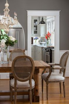 This deep gray dining room blends country and traditional styles for a refined farmhouse look. A cream chandelier lends elegance to the space, while a country dining table maintains the space's farmhouse feel.