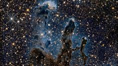 """A striking photo taken by the Hubble Space Telescope shows the """"Pillars of Creation"""" two decades after the cosmic columns of gas were first photographed."""