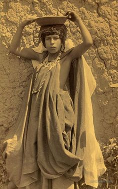 Young girl of Ouled Nail, wearing coin necklace, holding bowl on head. Algeria. 1860-1890