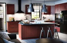 Ikea kitchen craft cabinet with dark color of maroon and black color kitchen craft cabinet with maroon color black granite countertop black metal cooker hood cooker gas stove metal sink and curved faucet black metal refrigerator oven microwave and stools