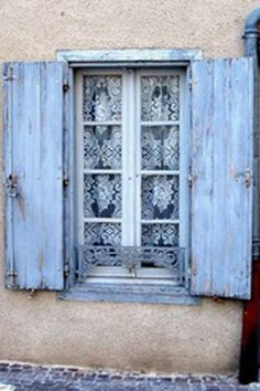 Aged pale blue shutters frame a charming window with lace curtains. An invitation for tea. Blue Shutters, Window Shutters, Cottage Shutters, Shutter Doors, Lace Curtains, Window Dressings, Window View, Through The Window, Old Doors