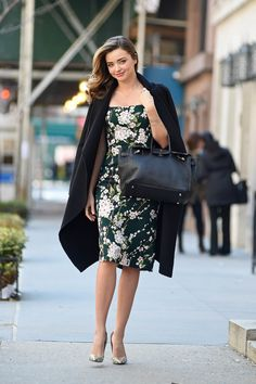 Miranda Kerr pairs her printed floral dress with a staple black coat.