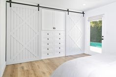 The master bedroom incorporates an ingenious barn door closet system. Drawers and cabinets provide storage in the center of the wall for folded clothes and accessories. Slide the barn doors over to reveal hanging room. Modern Farmhouse Style, Farmhouse Style Bedrooms, White Farmhouse, White Closet, Bedroom Office, Closet Bedroom, Attic Office, Master Closet, Closet Space