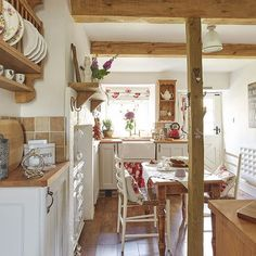 Exposed beams, shaker cabinetry, a belfast sink and pretty floral prints - what more could you want in a beautiful country kitchen?  Photograph: Jeremy Phillips