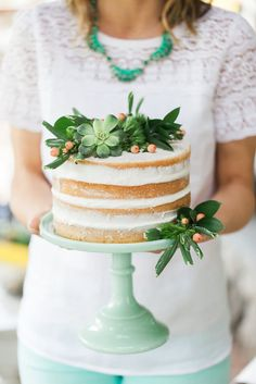 a simple naked cake topped with succulents and greenery.